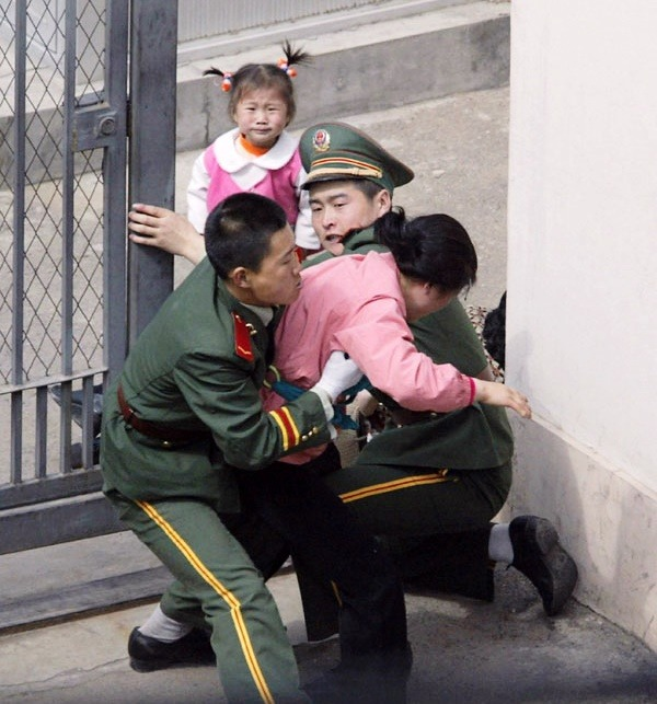 Kim Han-mi watches her mother being dragged by Chinese policemen when her family attempted to enter into the Japanese Consulate in order to seek asylum in Shenyang in this photo taken by Kyodo